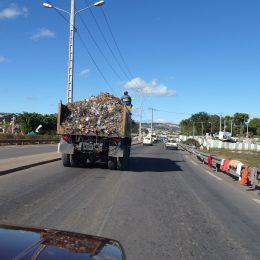 Müllabfuhr mit Müllwerker auf dem Dach der Fahrerkabine sitzend.