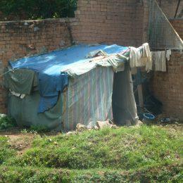 Improvisierte Baracke aus alten Lumpen und Planen irgendwo an einer Hauswand in Tana.