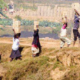 Frauen und Mädchen transportieren die Ziegel